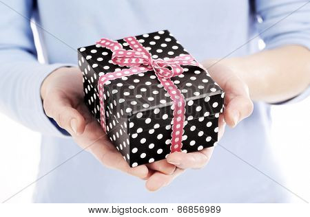 dotted present box with ribbon in a woman hand