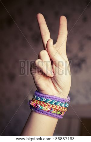 Child Hand Showing Victory Sign With Rainbow Loom Bracelets