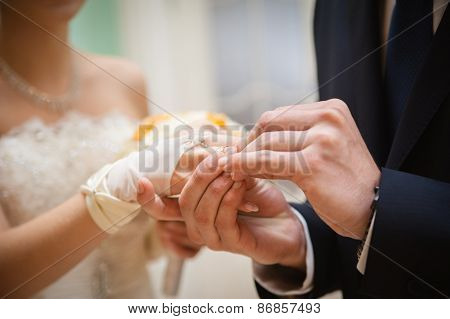 bride and groom are changing rings