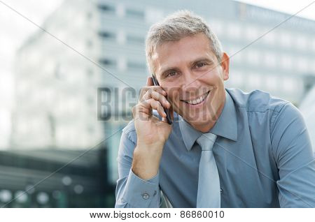 Closeup Of A Happy Mature Businessman Talking On Mobile
