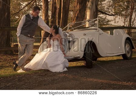 Young newly wed couple outdoors with vintage car
