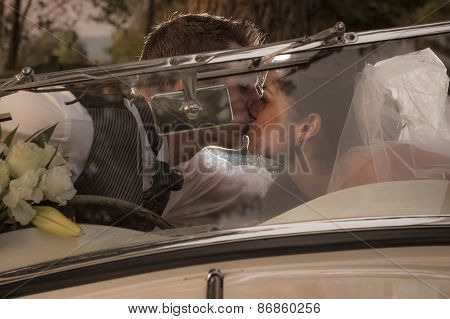 Newly wed couple sharing a kiss through a vintage car windscreen
