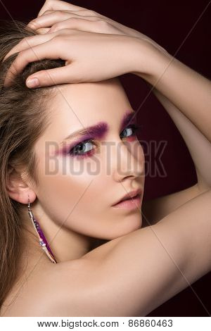 Beauty portrait of young brunette woman with feather earring
