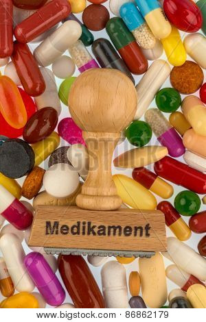 stamp on colorful tablets, symbolic photo for drug therapy and prescription