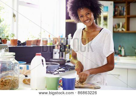 Young Woman Wearing Pajamas Preparing Breakfast In Kitchen