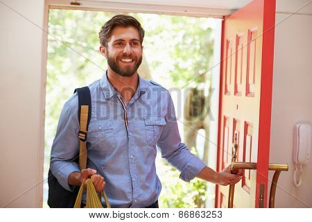 Young Man Returning Home For Work With Shopping