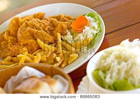 French fries with breaded meat and salad