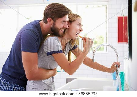 Couple In Pajamas Brushing Teeth In Bathroom