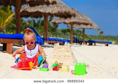 cute little girl building sandcastle on summer beach
