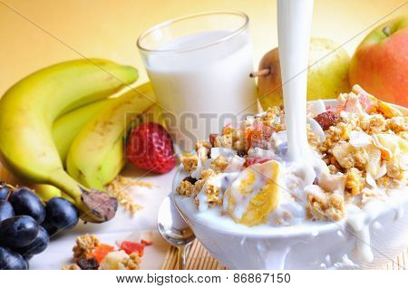 Stream Of Milk Falling Into A Bowl Of Cereal And Fruits