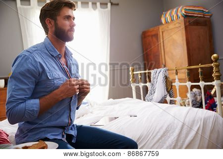 Man Sitting On Bed Getting Dressed In Morning