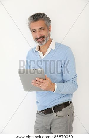 Handsome mature man websurfing with tablet, isolated