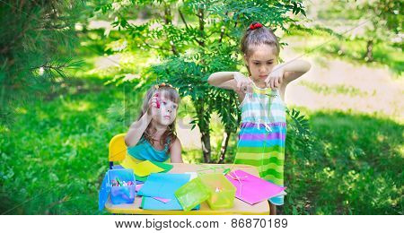 Girls, Sisters, Kids, Friends Cutting Multicolored Paper Outdoors In Summer