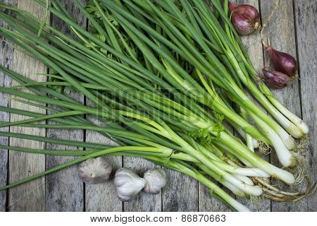 Onions Garlics And Welsh Onion On Wood Plank