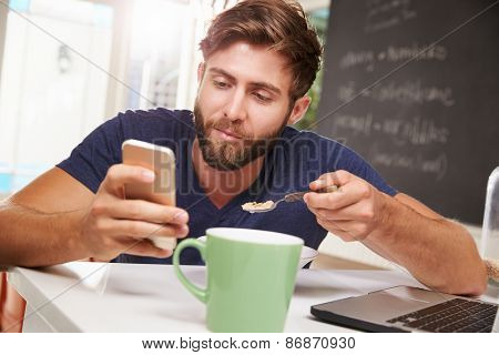 Man Eating Breakfast Whilst Using Mobile Phone And Laptop