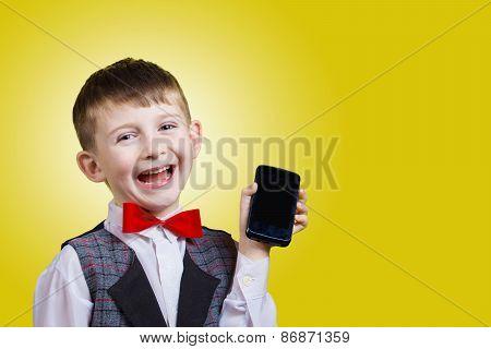Joyful beautiful little boy holding mobile
