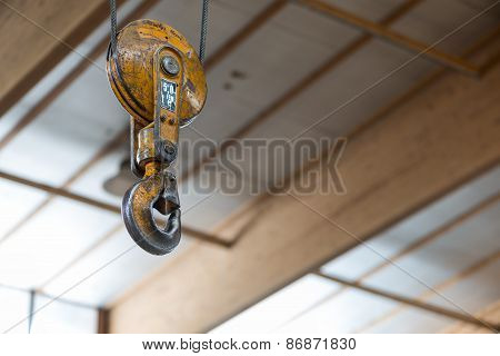 yellow clevis sling load hook with latch of carpentry workshop