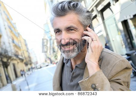 Mature man talking on the phone in the street