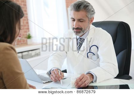 Doctor giving prescription to patient
