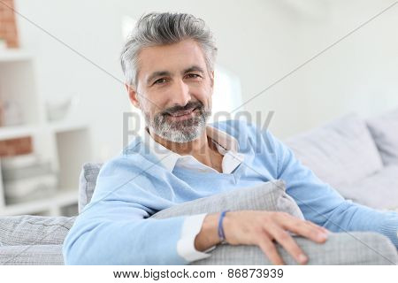 45-year-old man relaxing in sofa at home