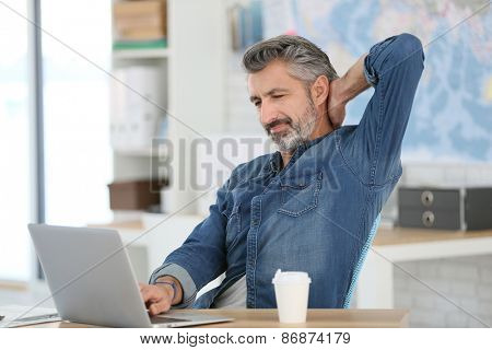Mature man relaxing in front of laptop in class