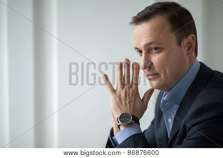 Attractive business man sitting pensively looking out the window