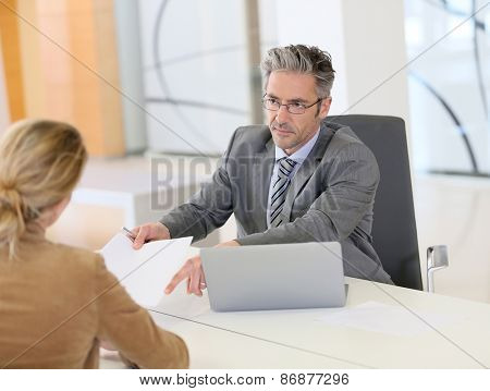 Woman meeting with banker and signing contract