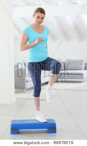 Middle-aged woman doing step exercices at home