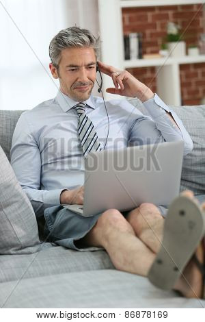Businessman with headset working from home on couch