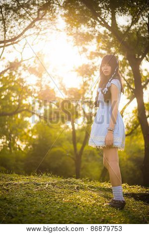 Cute Asian Thai Girl Is Standing In The Evening Sunset Through The Wilderness
