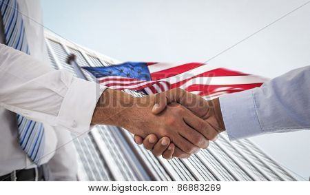 Close-up shot of a handshake in office against american flag and skyscraper