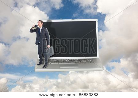 Businessman looking through binoculars against blue sky with white clouds