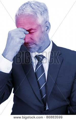 Upset mature businessman closing his eyes and holding his head on white background