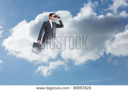 Businessman looking through binoculars against cloudy sky