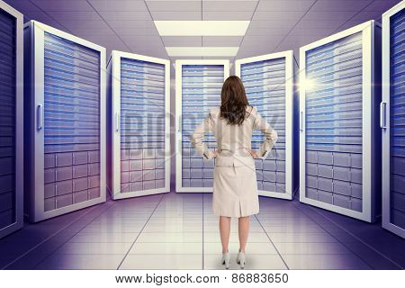 Businesswoman standing back to camera against digitally generated server room with towers