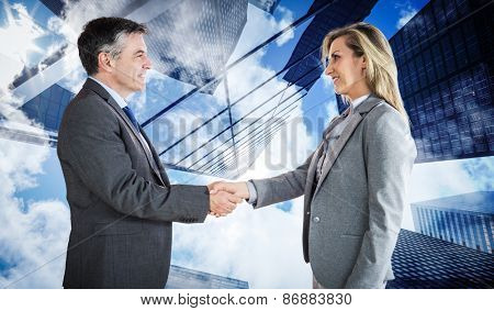 Pleased businessman shaking the hand of content businesswoman against skyscraper