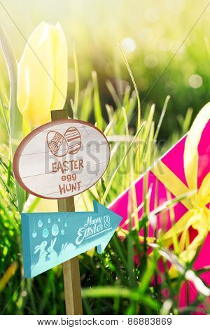 Easter egg hunt sign against pink gift box with yellow easter egg and yellow tulip