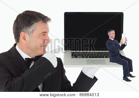 Businessman reading against waiter pointing to laptop