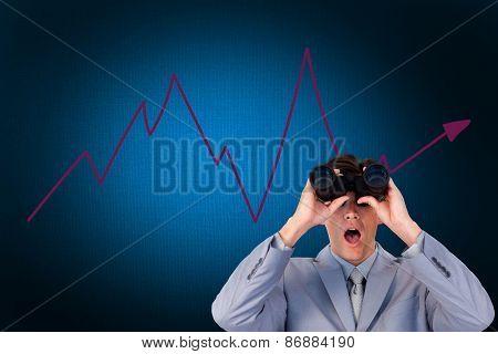 Suprised businessman looking through binoculars against digitally generated grey background