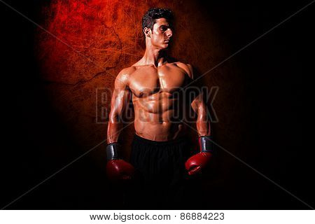 Muscular boxer against dark background
