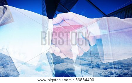 Side view of business peoples hands shaking against skyscraper