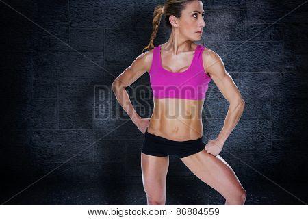 Female bodybuilder posing in sports bra and shorts against black background