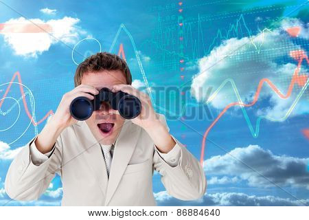 Positive businessman using binoculars against stocks and shares on black background