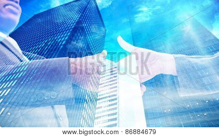 Businessman going shaking a hand against low angle view of skyscrapers