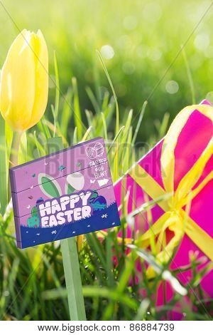 Easter egg hunt sign against pink gift box with yellow easter egg and tulip