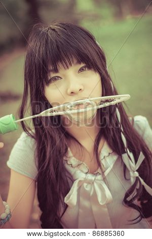 Cute Asian Thai Girl Is Blowing A Big Soap Bubble  In Vintage Color. Focus On Model Face.