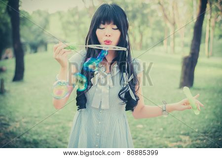Cute Asian Thai Girl Is Blowing A Soap Bubbles In The Park In Dreamy Color