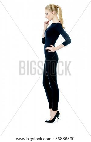 Full length portrait of a beautiful slender female model in black fitting clothing posing over white background. Beauty, fashion. Body care. Isolated over white.