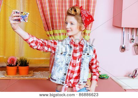 Pretty pin-up girl teenager taking picture of herself on a pink kitchen. Beauty, youth fashion. Pin-up style. Selfie.