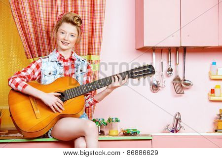 Cute pin-up girl teenager playing guitar on a pink kitchen. Beauty, youth fashion. Pin-up style.